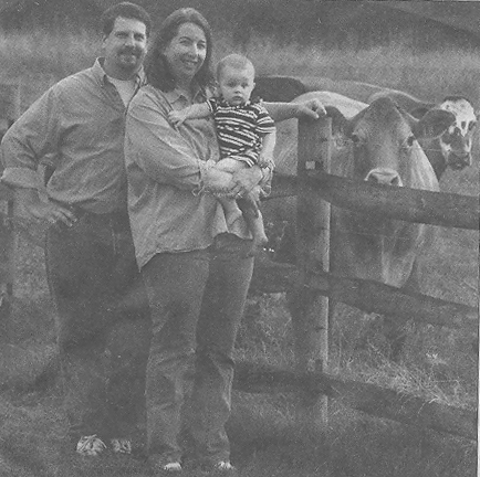 Andrew and Natalie Hammer, along with their son Joshua, pose with a couple of the 50 some beefalo at their farm. Photo by Glenn B. Dettman